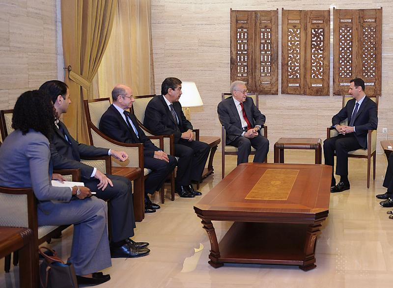 In this photo released by the Syrian official news agency SANA, Syrian President Bashar Assad, right, meets with the U.N.-Arab League envoy Lakhdar Brahimi, second right, in Damascus, Syria, Saturday Sept. 15, 2012. The new international envoy tasked with ending Syria's civil war says the country's conflict is a threat to world peace. (AP Photo/SANA)