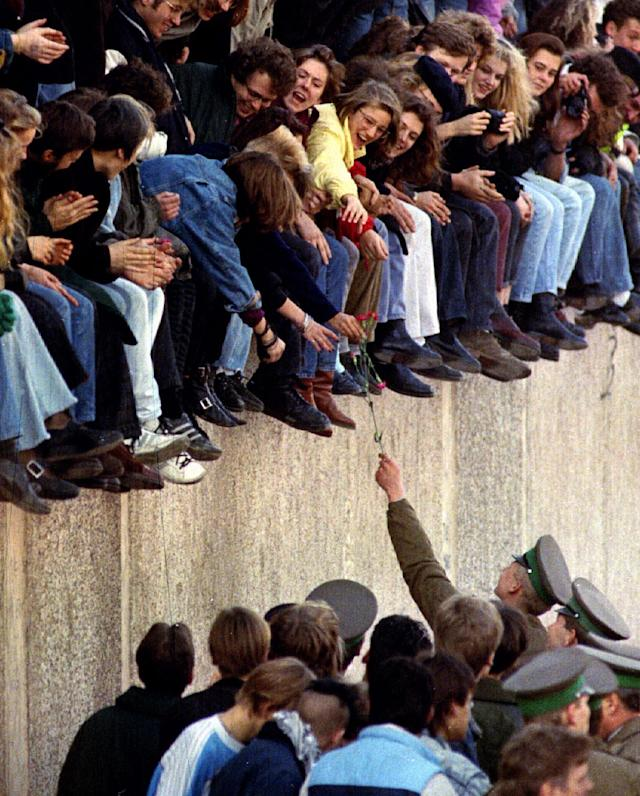 An East Berlin border guard hands a flower back to West Berlin citizens sitting atop the Berlin Wall in front of the Brandenburg Gate. (Photo: Reuters)