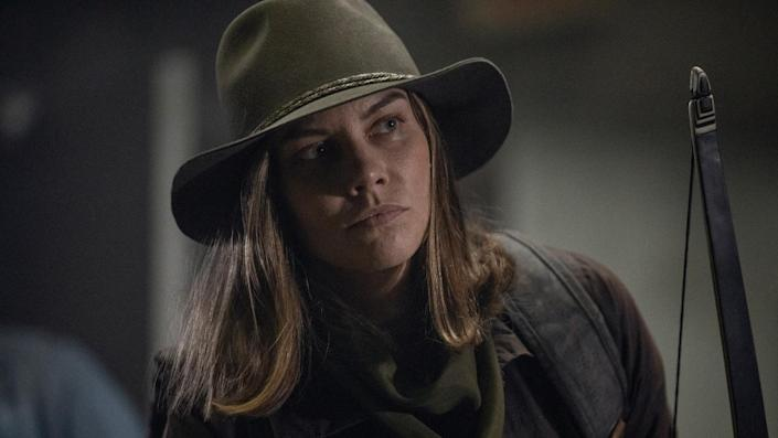Maggie from The Walking Dead TV show stands in a room wearing a brown hat