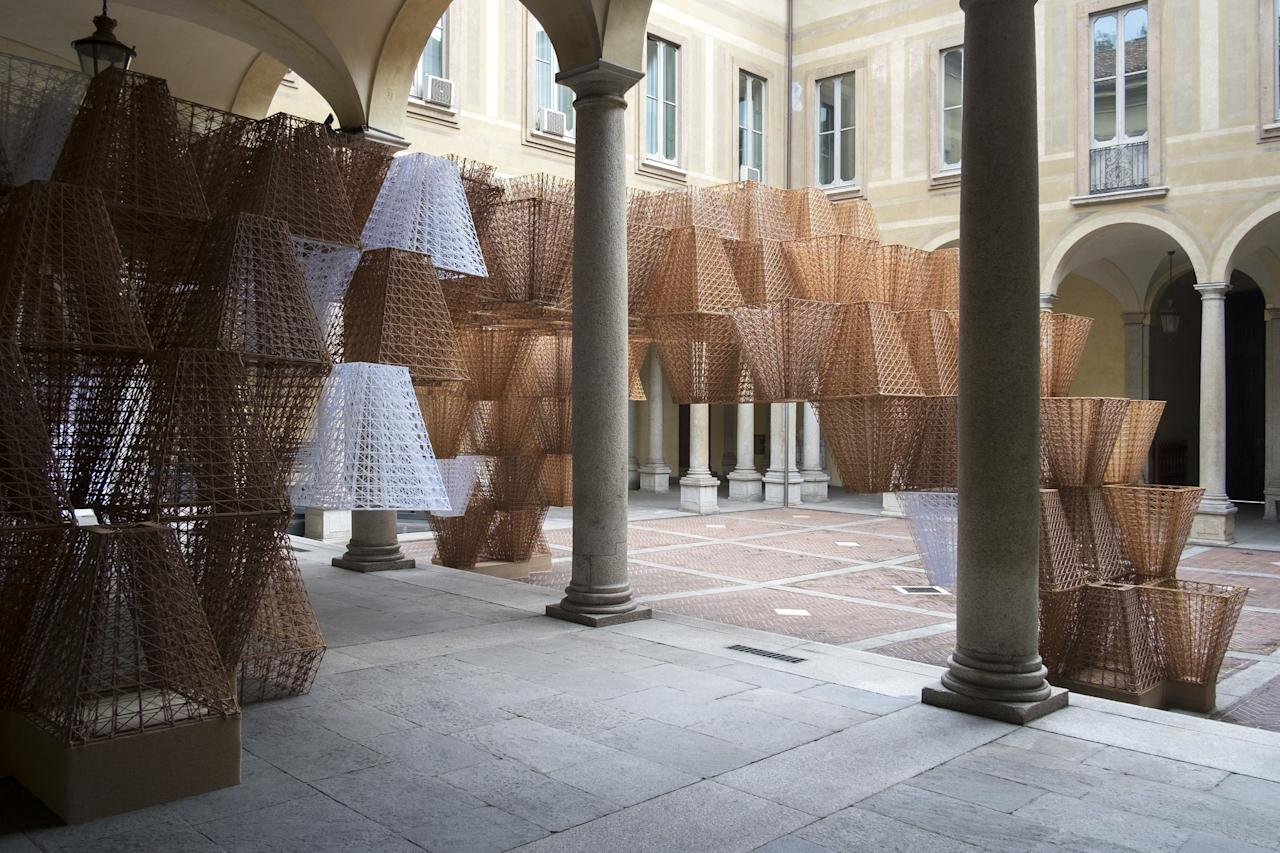 """From afar, the woven """"bricks"""" at <a href=""""https://www.cosstores.com/en_usd/explore/projects/event/cos-x-mamou-mani.html"""" rel=""""nofollow"""">Cos</a>'s eighth Salone del Mobile installation, a collaboration with architecture firm Mamou-Mani, look as if they're woven from straw. Nope. The cone-like shapes are actually 3D-printed out of fully compostable plastic made using renewable resources. To bring the structures to life, they created open-source software inspired by silkworms' cocoons. Set against the architecture of the 16th-century Palazzo Isimbardi, the exhibit feels extra futuristic. We've officially caught the 3D-printing fever, and it's time to put our money where our mouths are by buying things like <a href=""""https://www.gantri.com/products/10036/maskor-table-light-by-muka-design-lab"""" rel=""""nofollow"""">a seashell-inspired lamp 3D-printed from corn‑based materials</a>."""