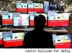 a man looks at tvs - best time to buy a tv