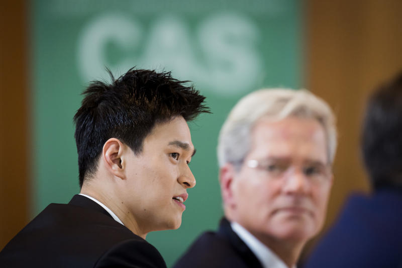 Swimmer Sun Yang, left, from China, attends a public hearing at the Court of Arbitration for Sport (CAS) in Montreux, Switzerland, Friday, Nov. 15 2019. One of China's biggest Olympic stars and three-time gold medalist swimmer Sun Yang is facing a World Anti-Doping Agency appeal in Switzerland that seeks to ban him for up eight years for allegedly refusing to give samples voluntarily. (Jean-Christophe Bott/Keystone via AP)