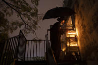 An ultra-Orthodox Jewish yeshiva student lights candles under an umbrella in the rain during the Jewish holiday of Hanukkah in the ultra-Orthodox city of Bnei Brak near Tel Aviv, Israel, Wednesday, Dec. 16, 2020. (AP Photo/Oded Balilty)