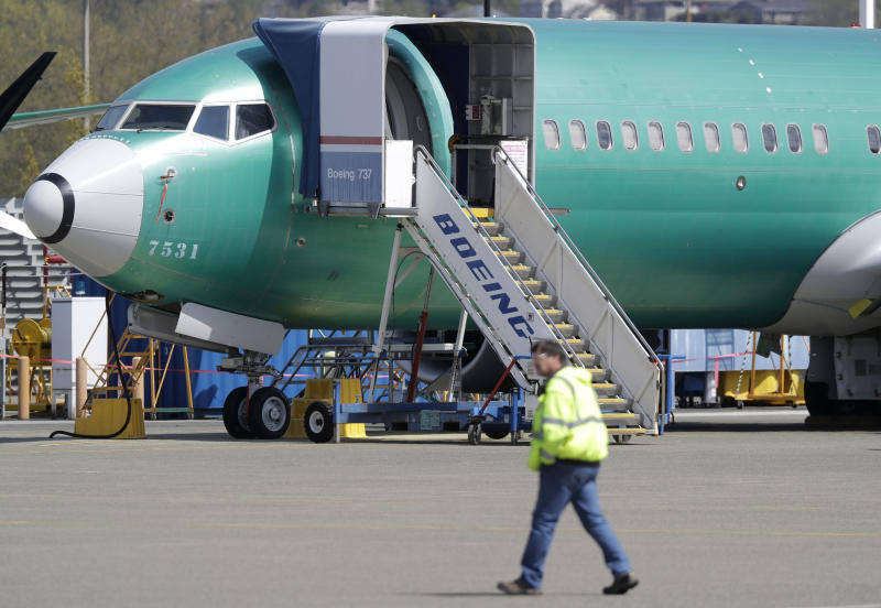 FILE - In this April 26, 2019, file photo a worker walks past a Boeing 737 MAX 8 airplane being built for Oman Air at Boeing's assembly facility in Renton, Wash. Boeing Co. reports financial earns on Wednesday, Oct. 23. (AP Photo/Ted S. Warren, File)