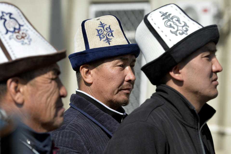 Protesters wearing Kyrgyz national hats listen to a speaker during a rally in front of the government building, in Bishkek, Kyrgyzstan, Wednesday, Oct. 14, 2020. Kyrgyzstan's embattled president has discussed his possible resignation with his newly appointed prime minister in a bid to end the political crisis in the Central Asian country after a disputed parliamentary election. President Sooronbai Jeenbekov held talks with Prime Minister Sadyr Zhaparov a day after refusing to appoint him to the post over concerns whether parliament could legitimately nominate him. (AP Photo/Vladimir Voronin)