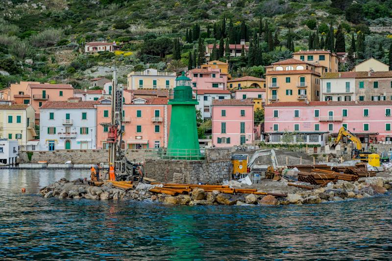 Pictured are colourful houses and a green lighthouse on the coast of Giglio.