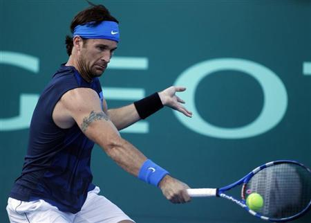 Moya of Spain returns the ball during his farewell exhibition tennis match against Canas of Argentina in Buenos Aires