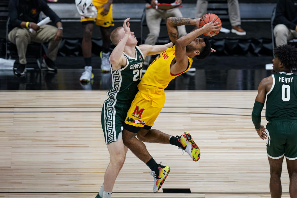 Maryland guard Eric Ayala (5) hits a shot over Michigan State forward Joey Hauser (20) in the second half of an NCAA college basketball game at the Big Ten Conference tournament in Indianapolis, Thursday, March 11, 2021. (AP Photo/Michael Conroy)