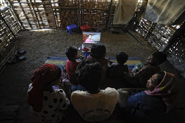 In this Nov. 29, 2013 photo, members of Senwara Begum's family watch her video interview at the Ohn Taw refugee camp on the outskirts of Sittwe, Myanmar. After their tiny Muslim village in Myanmar's northwest Rakhine had been destroyed in a fire set by an angry Buddhist mob, Senwara, 9, and brother, Mohamed, 15, became separated from the family. (AP Photo/Kaung Htet)