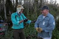 Thomas Aycock talks with a fellow hunter as they explore the Everglades' swamps looking for Burmese pythons, in Ochopee
