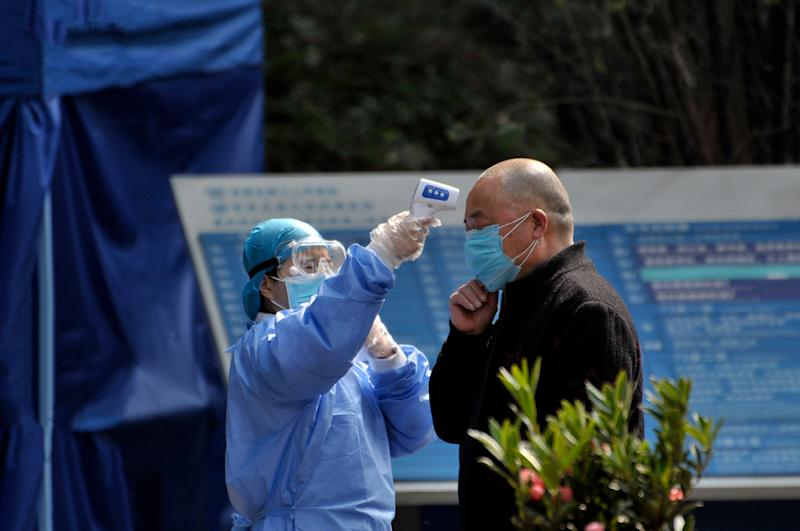 Chengdu/China-Feb.2020: New type coronavirus pneumonia in Wuhan has been spreading into many cities in China. Wearing masks, people lined up for temperature checks before entering hospital in Chengdu,China