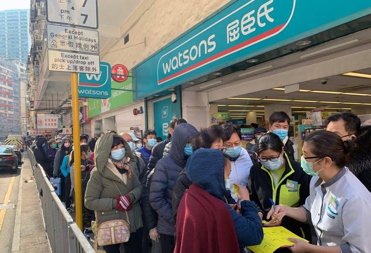 """<span class=""""caption"""">People queue outside a Watsons pharmacy in Hong Kong.</span> <span class=""""attribution""""><a class=""""link rapid-noclick-resp"""" href=""""https://www.shutterstock.com/image-photo/hong-kong-30-january-2020-people-1630888825"""" rel=""""nofollow noopener"""" target=""""_blank"""" data-ylk=""""slk:Lewis Tse Pui Lung/Shutterstock"""">Lewis Tse Pui Lung/Shutterstock</a></span>"""