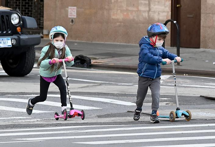 Children wearing face masks play on their scooters during the coronavirus pandemic on April 25, 2020 in New York City. (Photo by Jamie McCarthy/Getty Images)