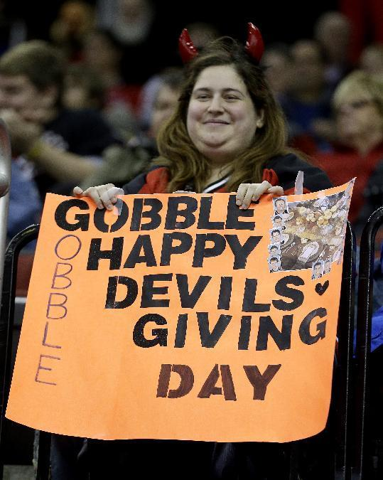 A spectator holds a sign during the second period of an NHL hockey game between the New Jersey Devils and the Carolina Hurricanes, Wednesday, Nov. 27, 2013, in Newark, N.J. (AP Photo/Julio Cortez)