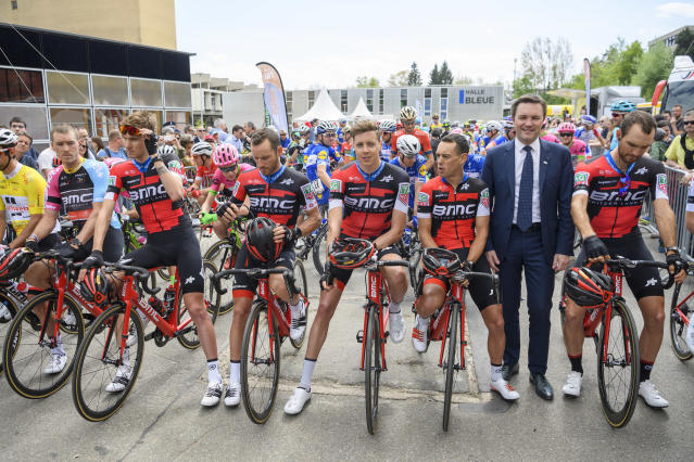 The cycling team BMC during a minute of silence in tribute of the dead BMC boss Andy Rihs with UCI President David Lappartient, right, during the first stage, a 166,6 km race between Fribourg and Delemont during the 72th Tour de Romandie UCI ProTour cycling race in Delemont, Switzerland, Wednesday, April 25, 2018. (Jean-Christophe Bott/Keystone via AP)