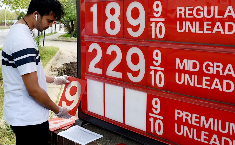 An employee of a gas station adjusts gasoline pump prices as they continue to fall with the oil market in turmoil on April 21, 2020, in Arlington, Virginia.(Photo by Olivier DOULIERY / AFP)