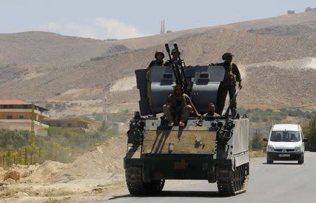 Lebanese army soldiers sit atop of an armoured carrier at the entrance of the Sunni Muslim border town of Arsal, in eastern Bekaa Valley August 5, 2014. REUTERS/Hassan Abdallah