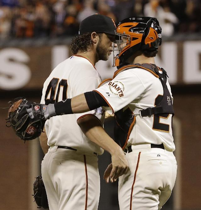San Francisco Giants catcher Buster Posey huhgs pitcher Madison Bumgarner after defeating the Kansas City Royals 5-0 in Game 5 of baseball's World Series Sunday, Oct. 26, 2014, in San Francisco. The Giants lead 3-2 in the series. (AP Photo/Matt Slocum)