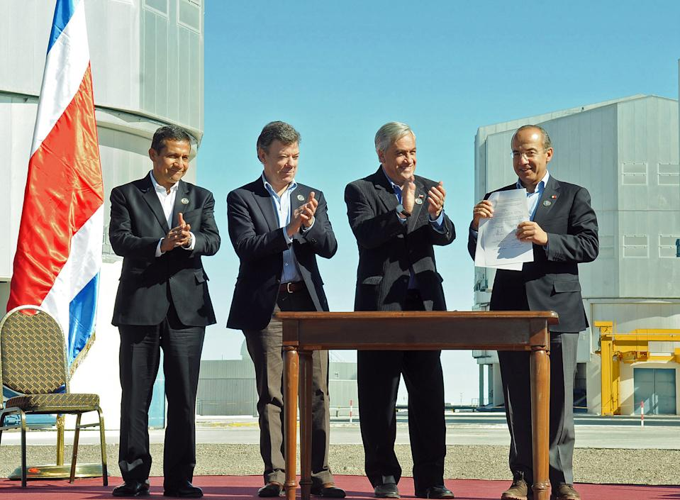 <p> In this picture released by Chile's Presidential Press Office, Mexico's President Felipe Calderon, right, holds up a signed document as Chile's President Sebastian Pinera, second from right, Colombia's President Juan Manuel Santos, second from left, and Peru's President Ollanta Humala, left, applaud at the signing ceremony of the accords reached at the IV Pacific Alliance Summit at the Paranal Observatory in Antofagasta, Chile, Wednesday, June 6, 2012. (AP Photo/Chile's Presidential Press Office, Luis Manuel de la Maza) </p>