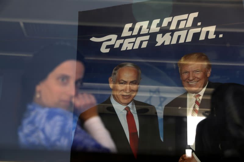 FILE PHOTO: An ultra-orthodox Jewish woman is seen through a bus window along with a reflection of a Likud party election campaign banner depicting Israeli Prime Minister Benjamin Netanyahu and U.S. President Donald Trump in Bnei Brak, Israel