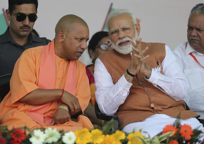 Prime Minister Narendra Modi speaks with the chief minister of Uttar Pradesh at a campaign rally in 2019.