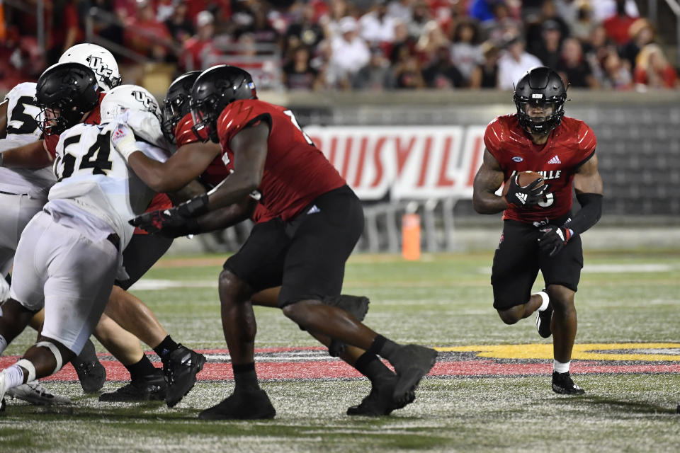 Louisville running back Jalen Mitchell (15) runs through an opening in the Central Florida line during the second half of an NCAA college football game in Louisville, Ky., Friday, Sept. 17, 2021. (AP Photo/Timothy D. Easley)