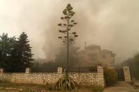 A house is on fire in Afidnes village, about 31 kilometres (19 miles), north of Athens, Greece, Friday, Aug. 6, 2021. Thousands of people fled wildfires burning out of control in Greece and Turkey on Friday, as a protracted heat wave turned forests into tinderboxes and flames threatened populated areas, electricity installations and historic sites. (AP Photo/Thanassis Stavrakis)