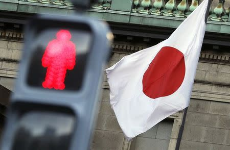 Japan's national flag is seen behind a traffic signal of a red man at the Bank of Japan headquarters in Tokyo November 19, 2014. REUTERS/Yuya Shino