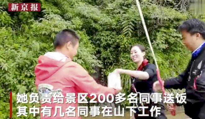 Wan hands over the hot meals at the bottom of the cliff. Photo: Weibo