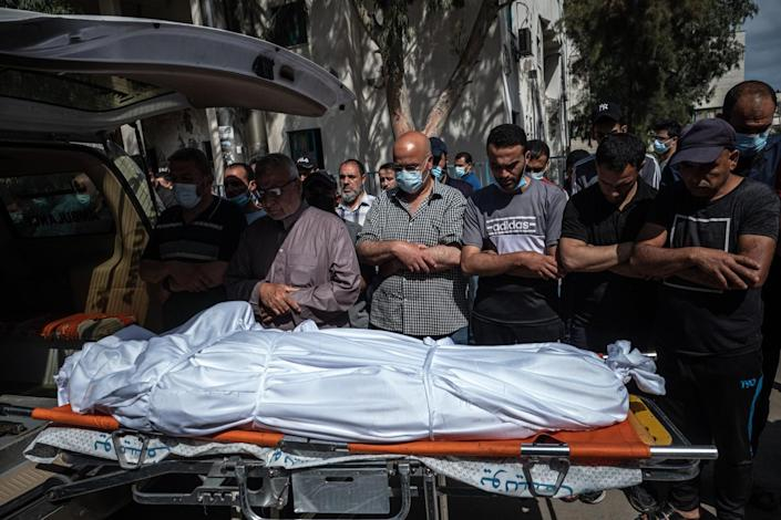 Palestinians perform funeral prayers over a wrapped body