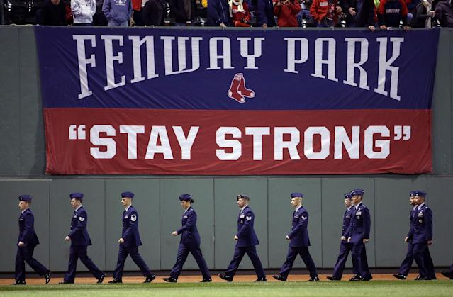 Military personal walk onto the field before Game 1 of baseball's World Series between the Boston Red Sox and the St. Louis Cardinals Wednesday, Oct. 23, 2013, in Boston. (AP Photo/Matt Slocum)