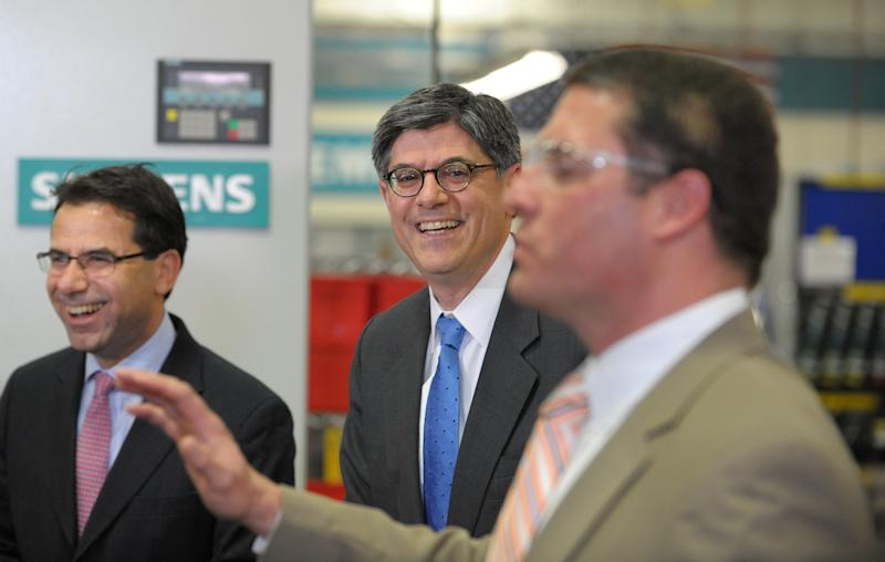 Treasury Secretary Jacob Lew, center, smiles as he and Siemens Industry North America CEO Helmuth Ludwig are introduced at the Alpharetta, Ga., electrical drive assembly plant after a tour of the facility, Thursday, March 14, 2013. (AP Photo/David Tulis)