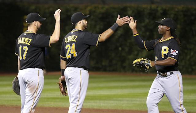 The Pittsburgh Pirates' Gaby Sanchez (17), Pedro Alvarez, and Andrew McCutchen celebrate the Pirates' 8-2 win over the Chicago Cubs after a baseball game Tuesday, Sept. 24, 2013, in Chicago. (AP Photo/Charles Rex Arbogast)
