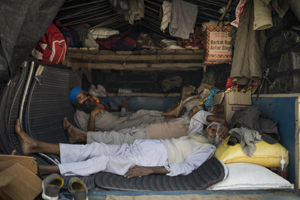 "Farmers rest in the back of their tractor trailer as they block a major highway during a protest to abolish new farming laws they say will result in exploitation by corporations, eventually rendering them landless, at the Delhi-Haryana state border, India, Tuesday, Dec. 1, 2020. The busy, nonstop, arterial highways that connect most northern Indian towns to this city of 29 million people, now beat to the rhythm of never-heard-before cries of ""Inquilab Zindabad"" (""Long live the revolution""). Tens and thousands of farmers, with colorful distinctive turbans and long, flowing beards, have descended upon its borders where they commandeer wide swathes of roads. (AP Photo/Altaf Qadri)"