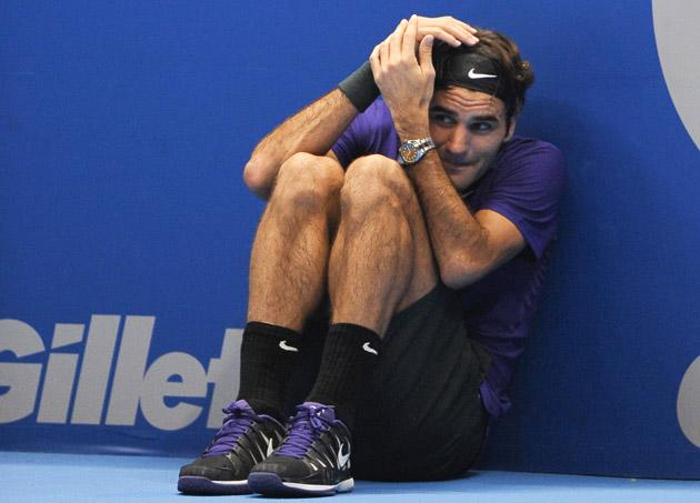 Swiss tennis player Roger Federer jokes to hide from a serve of French Jo-Wilfried Tsonga as he asks a ballboy to play for him during an exhibition match held at the Ibirapuera Gymnasium in Sao Paulo, Brazil, on December 8, 2012. AFP PHOTO/Yasuyoshi CHIBA