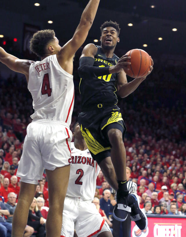 Oregon guard Victor Bailey Jr. (10) drives on Arizona center Chase Jeter in the first half of an NCAA college basketball game, Thursday, Jan. 17, 2019, in Tucson, Ariz. (AP Photo/Rick Scuteri)