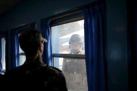 FILE PHOTO: North and South Korean soldiers look at each other through a window of a conference room in the United Nations Command Military Armistice Commission Conference Building at the truce village of Panmunjom