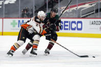 Anaheim Ducks defenseman Kevin Shattenkirk (22) and Anaheim Ducks center Rickard Rakell (67) vie for the puck during the second period of an NHL hockey game Wednesday, Feb. 24, 2021, in Glendale, Ariz. (AP Photo/Rick Scuteri)