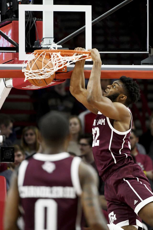 Texas A&M forward Josh Nebo (32) goes up to dunk over an Arkansas defender during the first half of an NCAA college basketball game, Saturday, Feb. 23, 2019, in Fayetteville, Ark. (AP Photo/Michael Woods)