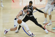 Los Angeles Clippers guard Paul George, right, defends against Dallas Mavericks guard Luka Doncic, left, during the first quarter of Game 7 of an NBA basketball first-round playoff series Sunday, June 6, 2021, in Los Angeles, Calif. (AP Photo/Ashley Landis)