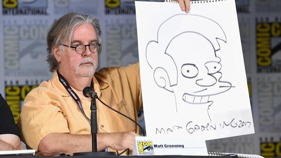 Matt Groening at the 2017 Comic-Con in San Diego, holding up a picture of Apu