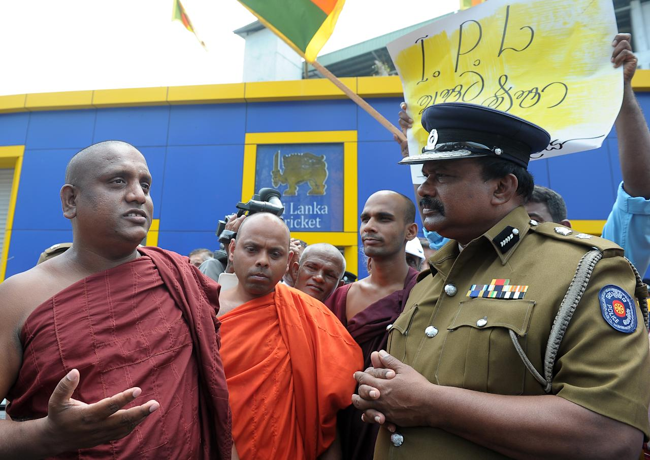 Sri Lankan Buddhist monks speak to reporters as police officials look on outside the Sri Lanka Cricket head office in Colombo on April 3, 2013. The monks oppose national team players visiting India to play in the Indian Premier League tournament amid a ban on them by the south Indian state of Tamil Nadu.   Sri Lanka's cricket board said that it would allow its players to take part in the IPL Twenty20 tournament in India next month after receiving assurances about their safety. The government in Colombo had threatened to prevent any of the 13 Sri Lankan players contracted to play in the Indian Premier League from taking part after they were all effectively barred from playing in the southern Indian state of Tamil Nadu.   AFP PHOTO/ LAKRUWAN WANNIARACHCHI        (Photo credit should read LAKRUWAN WANNIARACHCHI/AFP/Getty Images)