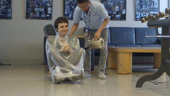 Science educator Tien Huynh-Dinh at the LIGO Science Education Center vacuum-wraps audio engineer Joe Chilcott in a demonstration of the atmospheric pressure humans live with, every day, on this planet at the LIGO Observatory in Livingston,