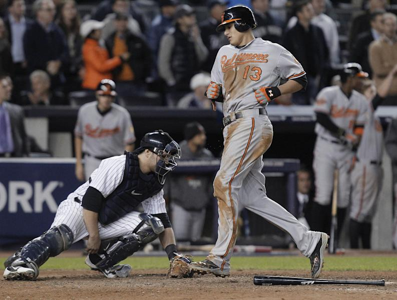 Baltimore Orioles' Manny Machado (13) runs past New York Yankees catcher Russell Martin as he scores on a double by J.J. Hardy during the 13 inning of Game 4 of the American League division baseball series Thursday, Oct. 11, 2012, in New York. The Orioles won 2-1. (AP Photo/Kathy Willens)