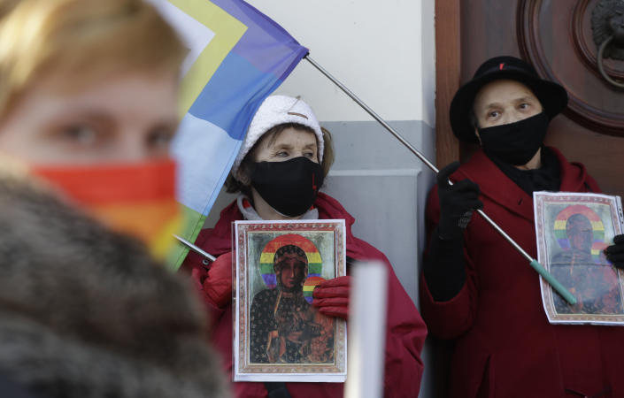Polish LGBT rights activists gather outside a court which acquitted three women who faced trial on accusations of desecration, in Plock, Poland, Tuesday March 2, 2021. A Polish court has acquitted three activists who had been accused of desecration for adding the LGBT rainbow to images of a revered Roman Catholic icon. In posters that they put up in protest in their city of Plock, the activists used the rainbow in place of halos on a revered image of the Virgin Mary and baby Jesus. (AP Photo/Czarek Sokolowski)