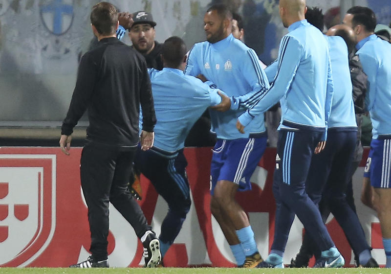 FILE - In this Thursday, Nov. 2, 2017 file photo, Marseille's Patrice Evra, third left, raises his foot trying to kick a man during a scuffle with Marseille supporters who trespassed onto the field before the Europa League group I soccer match between Vitoria SC and Olympique de Marseille at the D. Afonso Henriques stadium in Guimaraes, Portugal. UEFA has suspended Marseille defender Patrice Evra until June 2018 for kicking one his own team's fans before a Europa League game. (AP Photo/Luis Vieira, File)