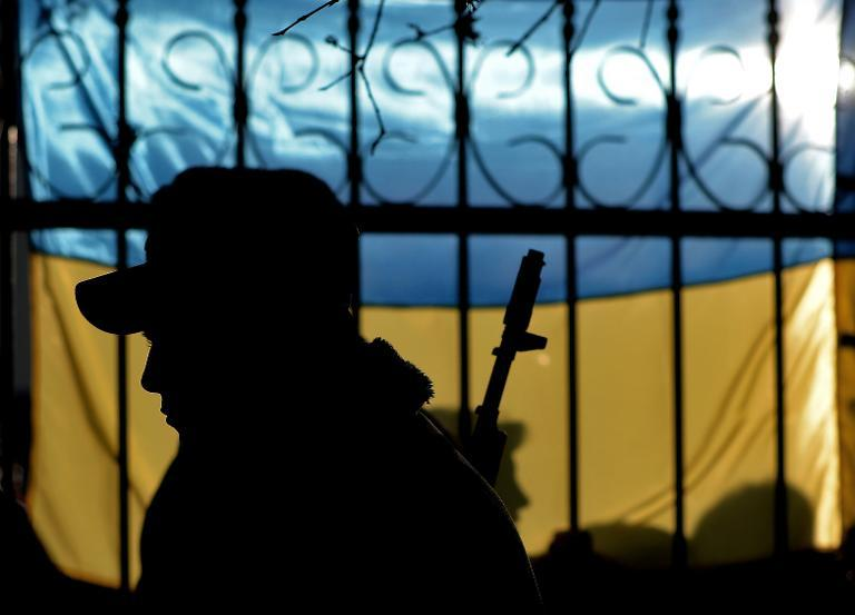 The silhouette of a Ukrainian soldier is seen against a Ukrainian flag in Sevastopol, on March 3, 2014