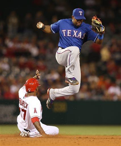 Texas Rangers shortstop Elvis Andrus leaps over Los Angeles Angels Howie Kendrick who is out at second base on a fielder's choice in the ninth inning of a baseball game in Anaheim, Calif., on Tuesday, April 23, 2013. (AP Photo/Christine Cotter)
