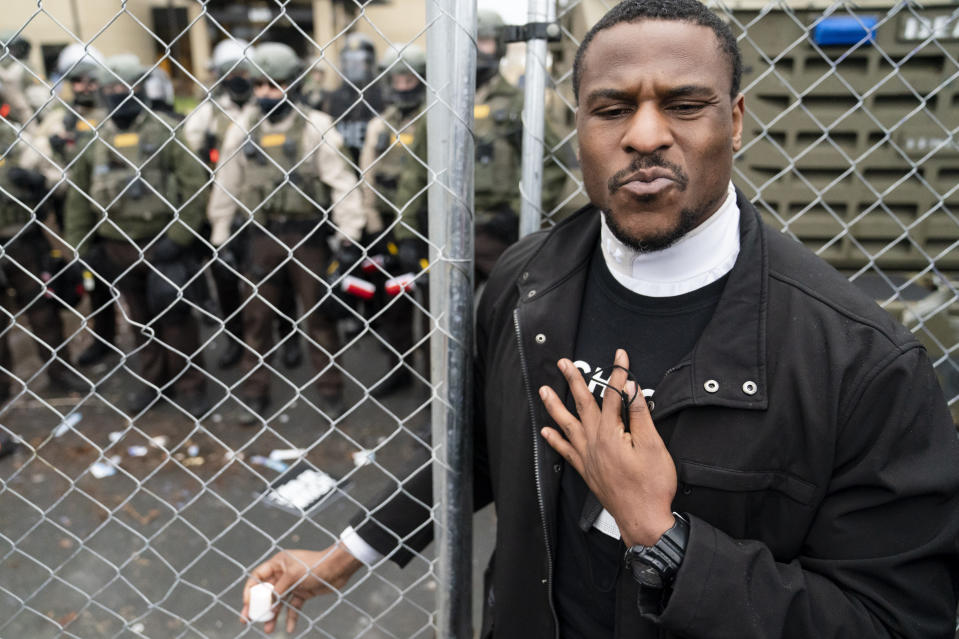 Michael Odiari attempts to calm demonstrators at a perimeter security fence as authorities prepare to engage during a protest decrying the shooting death of Daunte Wright outside the Brooklyn Center Police Department, Wednesday, April 14, 2021, in Brooklyn Center, Minn. (AP Photo/John Minchillo)