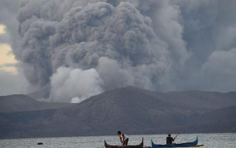 Residents living along Taal lake catch fish in the shadow of the volcano - Credit: Ted Aljibe/AFP